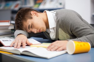 Tired student sleeping at the desk